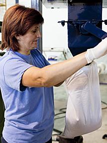 Una operaria rellena una almohada. | M. C.