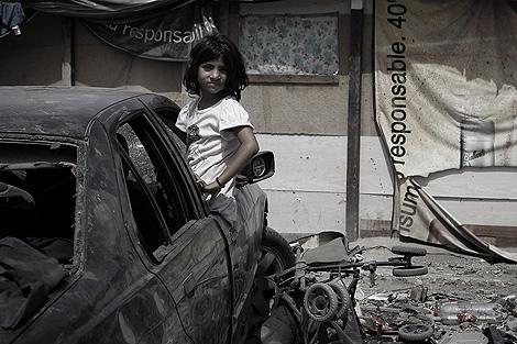 Una niña dentro de un coche abandonado en El Gallinero (Madrid).   Alberto di Lolli