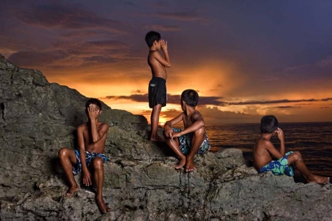 Luis, Salvador, Armando y JM, ocultan su rostro, y sus verdaderos nombres, para preservar su identidad: Posan al atardecer en Puerto Galera, Filipinas. © Isabel Muñoz