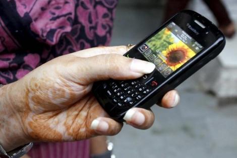 Una mujer sostiene una BlackBerry en Bhopal, India . | Efe