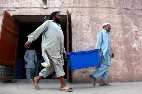 Trabajadores afganos cargan urnas electorales en un camión. | Efe