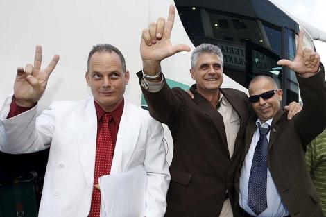 Tres de los últimos excarcelados saludan a su llegada a Madrid. | Efe