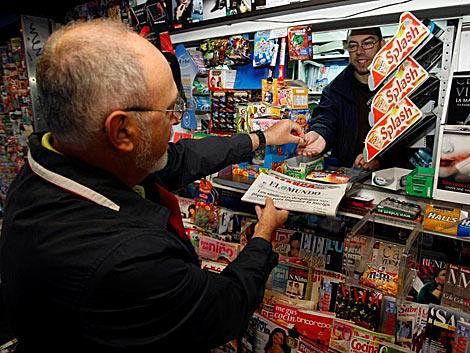 Un ciudadano compra El Mundo en el kiosko. | Diego Sinova.