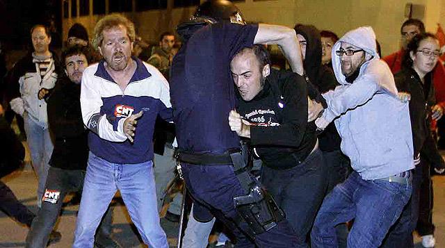 Policías antidisturbios intentan disolver a un grupo de piquetes que bloqueaban la salida de autobuses en Madrid. | Efe