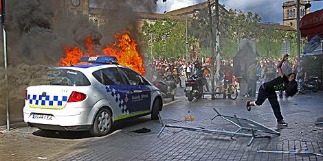 Disturbios en Barcelona, con un coche de la Guardia Urbana incendiado. | Christian Maury