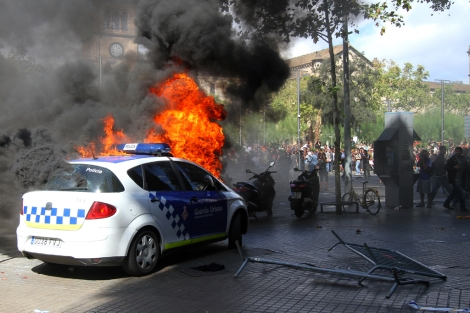 A police patrol car, set aflame, in Barcelona. | Christian Maury