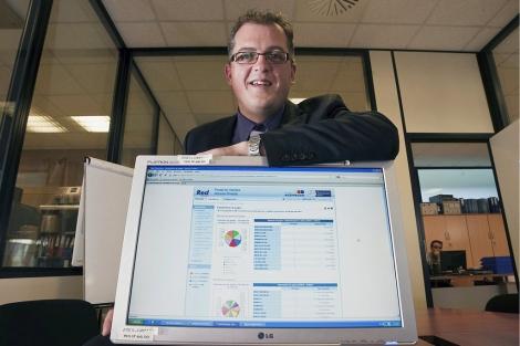 José Manuel Cuena detrás de una pantalla en la que aparecen todos los datos de tesorería de una compañía. | Pablo Requejo