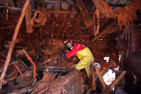 Un miembro de los equipos de limpieza, en una de las casas destrozadas. | Reuters