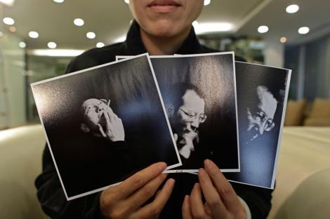 La mujer de Liu muestra tres imágenes de su marido preso. | Reuters
