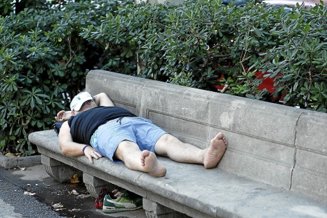 Un hombre se echa la siesta en un banco.   S. Cogolludo