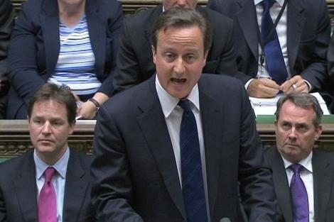 David Cameron junto a Nick Clegg (izqda.) y Liam Fox en el Parlamento. | Reuters