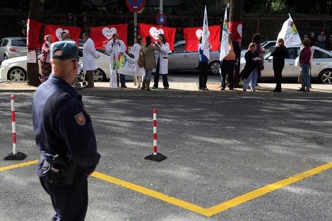 Un policía vigila la puerta del hotel con varios manifestantes en la acera. | Esther Lobato