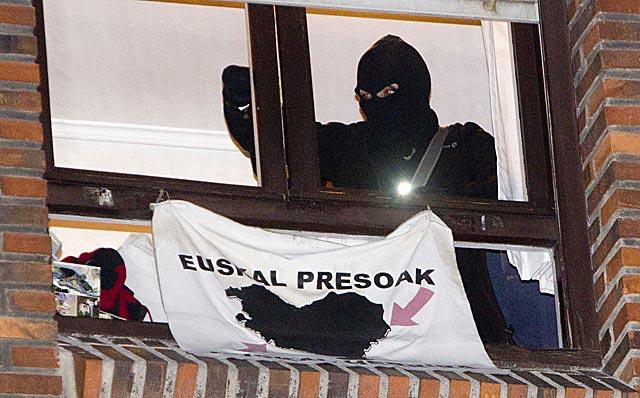 Un policía retira una pancarta proetarra de la ventana de un local de Bilbao.   Iñaki Andrés