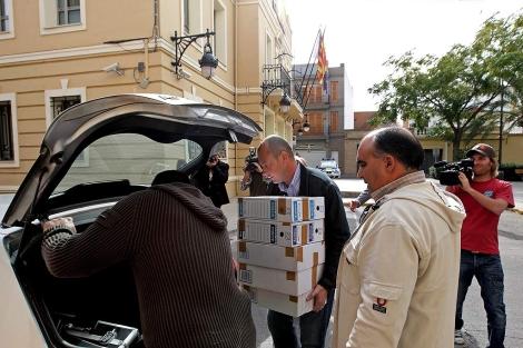 Agentes de la Policía salen del Ayuntamiento cargados con cajas. | Efe