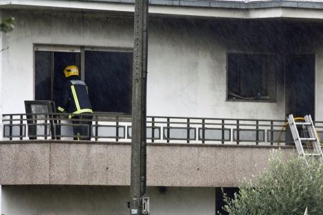Los bomberos inspeccionan la vivienda quemada donde murieron dos personas en Lalín. | Efe