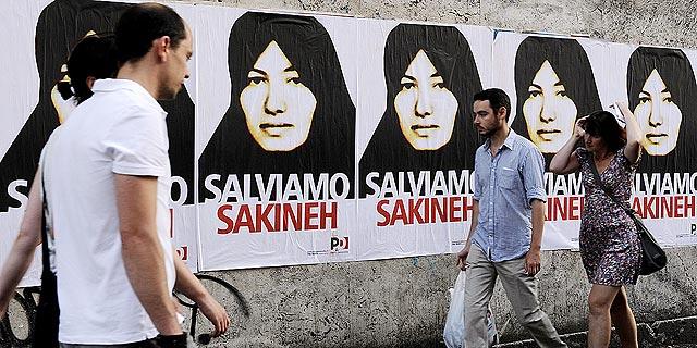 Jóvenes pasean frente a un cartel de apoyo a Sakineh en Roma. | Efe