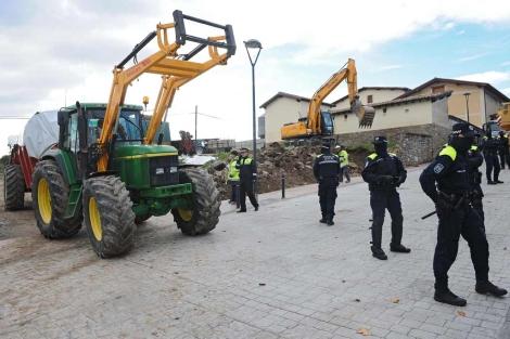 Un tractor de los propietarios sale mientras sigue trabajando la excavadora. | Nuria González