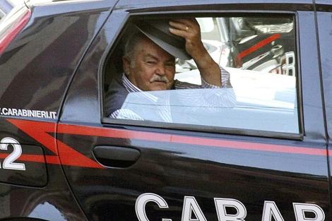 Un detenido por pertenecer a la N'Drangheta saluda desde un coche policial. | AP