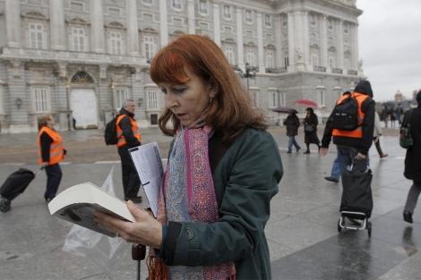 Una mujer ojea un libro en el 'Bookcrossing' de la Plaza de Oriente. | EFE