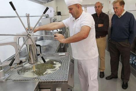 La familia Blanco muestra de cómo funciona la máquina que da churros, rosquillas y porras de Inblan. | J. M. Lostau