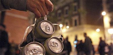 Un joven lleva un pack de cervezas por la noche.  El Mundo