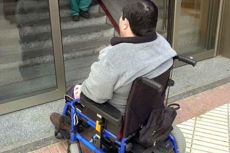 Una persona con discapacidad ante un portal sin rampa.   José Aymá