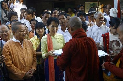 Suu Kyi realiza una ofrenda a un monge budista, hoy miércoles en Rangún. | Afp