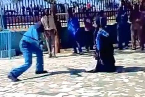 Uno de los hombres uniformados azota a la mujer.