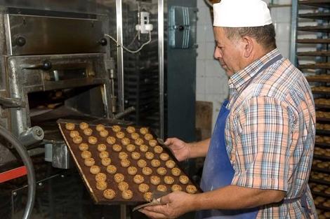 Un trabajador introduce una bandeja de mantecados en el horno. | Quino Castro