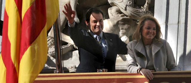 Mas y su mujer saludan desde el balcón del Palau de la Generalitat. | Efe