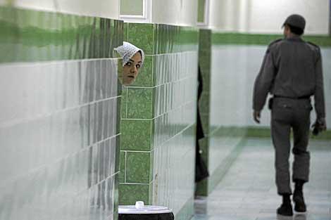 Una presa iraní se asoma mientras un guardia vigila la sección femenina de la cárcel de Evin. | Afp