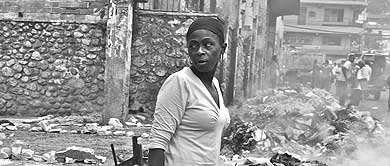 Una mujer haitiana junto a una pila de escombros. | Foto: Rui Ferreira