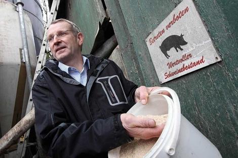 Un granjero muestra un cubo de pienso en Schlamersdorf. | AFP
