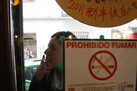 Una mujer fumando en la calle, tras la prohibición de fumar en cualquier espacio público. | J. B.
