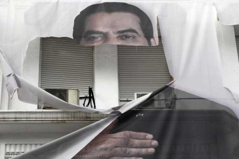 Una imagen medio destrozada de Ben Ali en Túnez.   Ap