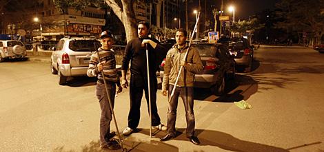 Tres jóvenes de El Cairo, armados contra el pillaje. | AFP
