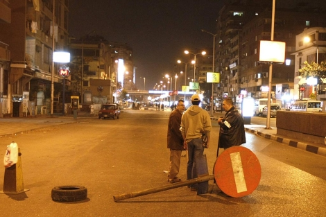 Tres ciudadanos hacen guardia para evitar el pillaje.   AFP
