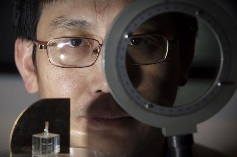 El investigador Shuang Zhang posa con su 'máquina de invisibilidad' .   Univ. de Birmingham