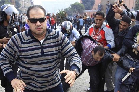 Un policía de civil corre a atacar a un periodista en El Cairo (Foto: Reuters)