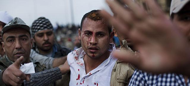 Un hombre sospechoso de ser un policía de paisano, escoltado por manifestantes anti Mubarak. | AP VEA MÁS FOTOS