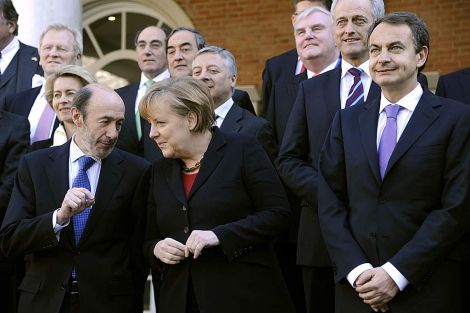 Rubalcaba conversa con Merkel, junto a Zapatero en la foto de familia.   AFP