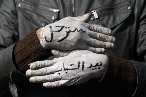 Un manifestante muestra palabras contra Mubarak escritas en los guantes. | Reuters