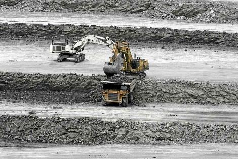 Una excavadora carga un camión con mineral en la explotación a cielo abierto. | Jesús Morón