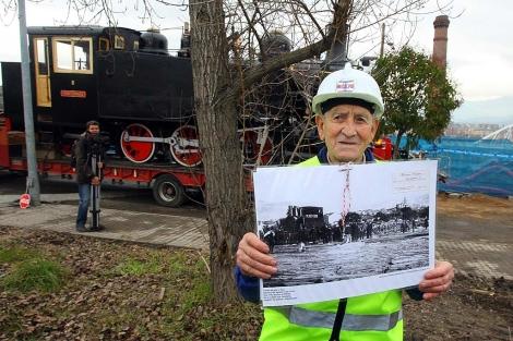 El último conductor de la locomotora, Marino Castro, con la 'joya' restaurada al fondo. | C.S. / ICAL