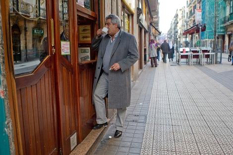 Un hombre fuma fuera de una cafetería mientras se toma un café. | Mitxi