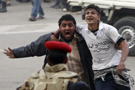 Dos jóvenes continúan las protestas en la plaza Tahrir. | Ap