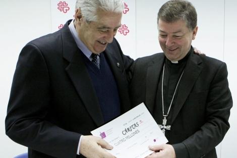 Monseñor Martínez Camino (dcha) entre al presidente de Cáritas el donativo. | Efe