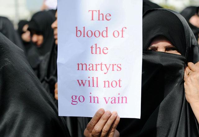 Una mujer sostiene un cartel donde se lee que 'la sangre de los mártires no será en vano' en Manama (Bahrein).   Efe