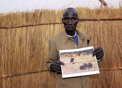 El padre del niño fotografiado por Carter sujeta la foto de su hijo. (A. Rojas)