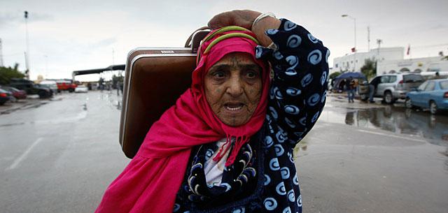 Una mujer tunecina huye de Libia por el paso de Ras Jdir.   Reuters